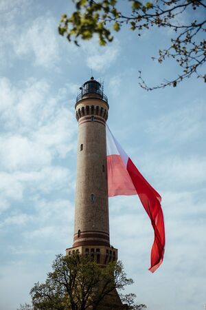 Old Brick Stone Lighthouse with polish national flag. Cloudy skies. Independent Day