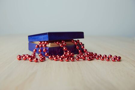 A photograph of gift box and red beads necklace on wooden background Standard-Bild - 129441499