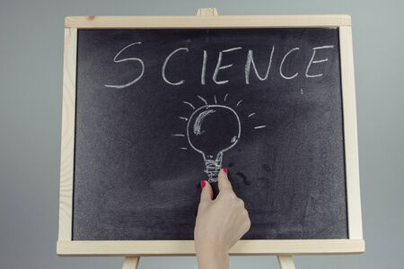 A teacher writing science, drawing chemistry elements on dark chalkboard by hand, gray background Banco de Imagens