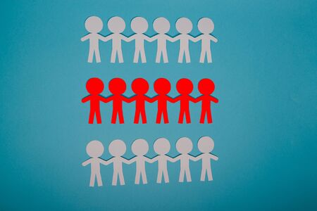 abstract paper people holding for hands on blue background Stock Photo