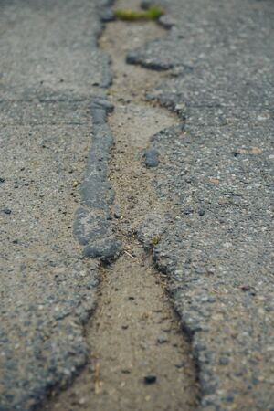 A road damaged by rain and snow, that is in need of maintenance. Broken asphalt pavement resulting in a pothole, dangerous to vehicles Banco de Imagens
