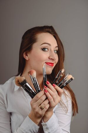 Woman holding a set of cosmetic brushes for make-up, isolated on gray Banco de Imagens