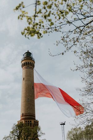 Polish flag hung on at historical lighthouse located in Swinoujscie, Poland, The construction was build in 1828 and height is 65 meters. 19th century. Top tallest Lighthouse in the World Stockfoto - 130754990