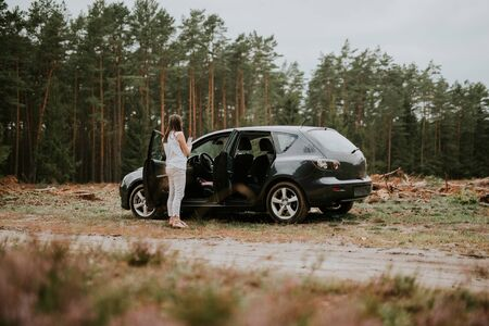 Young brunette woman standing by broken car in the forest.