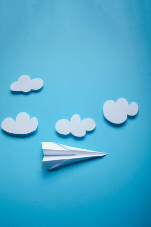 Paper plane in female hand on a blue background with clouds