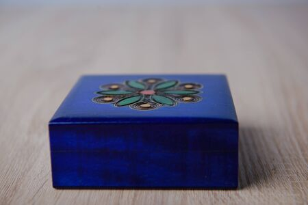 closed antique wooden blue jewelry box on the table.