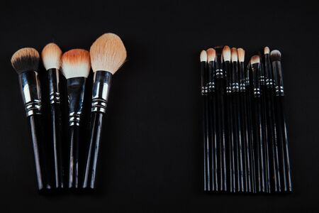 A photograph of Isolated make-up powder with brush on black background