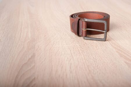 Leather belt on the wooden desk table