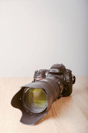 Digital photo camera on wooden desk table