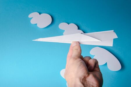 Paper plane in female hand on a blue background with clouds Stockfoto - 131502714