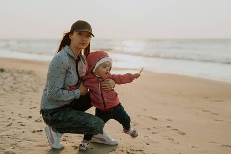 Mother and little daughter playing on the beach. Authentic image. Stock Photo
