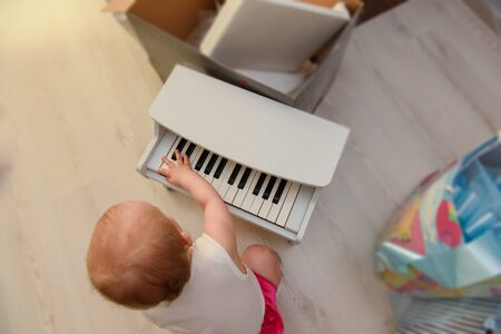 beautiful baby girl playing toy piano in light room. Authentic image.