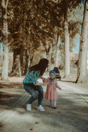 Happy mother and daughter in the park. Beauty nature scene with family outdoor lifestyle. Happy family resting together on the green grass, having fun outdoor. Happiness and harmony in family life. Stok Fotoğraf
