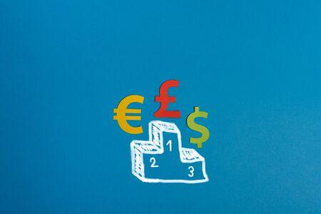 Paper symbols of euro, dollar and british pound currency on podium, blue background. View from above with copy space. Minimalistic simple concept Stock Photo
