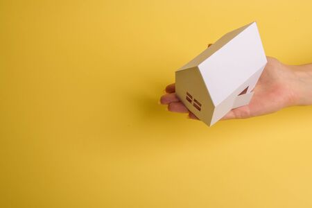White family paper house in man hand on yellow background paper. Minimalistic style. Copy space. View from above. Horizontal orientation Foto de archivo