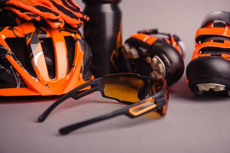 Helmet, gloves, shoes and water bottle - bicycle accessories. Orange color