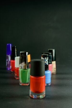 a photograph of coloured nail polish bottles on dark background
