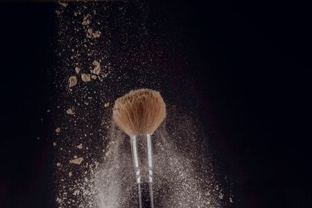 A photograph of Isolated make-up powder with brush on black background Archivio Fotografico - 133481090