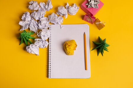 gift box and green origami trees with notepad on yellow desk, table Stock Photo