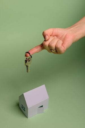 White family paper house. House keys in hand on mint background paper. Minimalistic and simple concept, style. Copy space. Vertical orientation. Family moving or removal concept.