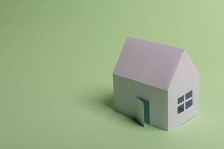 White family paper house in man hand on mint background paper. Minimalistic and simple concept, style. Copy space. Horizontal orientation 스톡 콘텐츠
