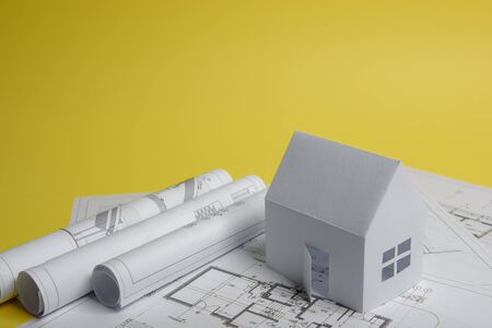 White family paper house, house projects plan and blueprints on yellow background paper. Minimalistic and simple concept, style. Vertical orientation.