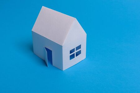 White family paper house over block of flats on blue background paper. Minimalistic and simple concept, style. Copy space. Vertical orientation. 스톡 콘텐츠