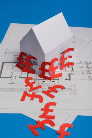 White family paper house , british pound money symbol , house projects plan and blueprints on mint background paper. Minimalistic and simple concept, style. Vertical orientation. View from above. copy 스톡 콘텐츠