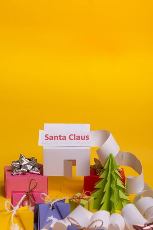 Long twisted expanded letter for Santa Claus. Copy space. yellow background. Santa Claus paper home at north pole. Stock Photo