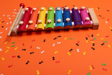 Wooden xylophone in rainbow colors for children an isolated on orange. Paper colorful musical notes surrounding .