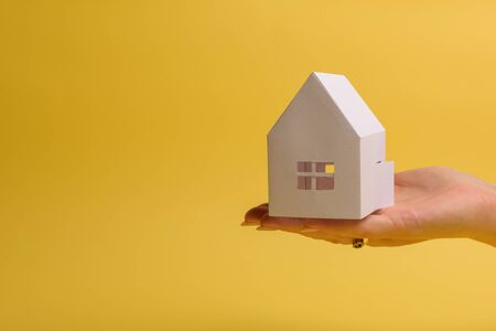 White family paper house in man hand on yellow background paper. Minimalistic style. Copy space. View from above. Horizontal orientation 스톡 콘텐츠
