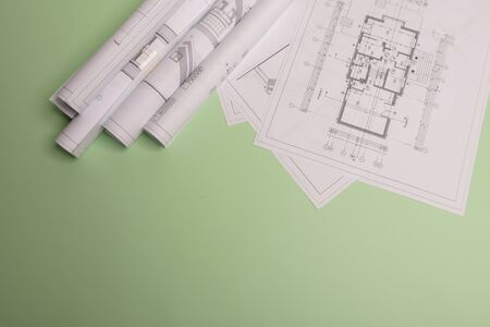 White family paper house , stack of money coins, house projects plan and blueprints on mint background paper. Minimalistic and simple concept, style. Horizontal orientation