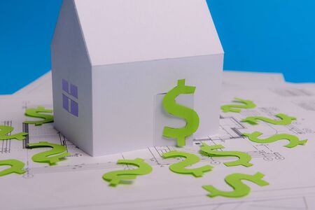 Paper skyscrapers , us dollar money, house projects plan and blueprints on blue background paper. Minimalistic and simple concept, style. Horizontal orientation. View from above. Copy space.