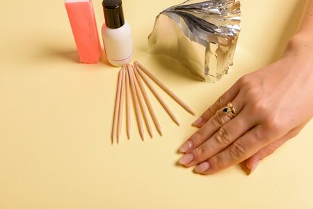 Hybrid manicure removal kit. The procedure for removing varnish from nails in progress