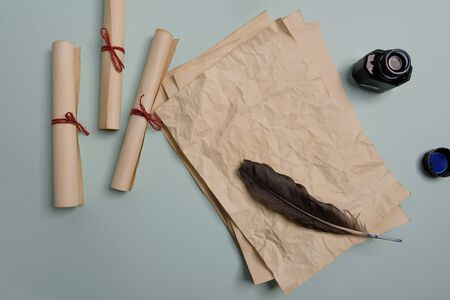 Raven feather, inkwell and old yellowed paper on red background. Copy space. Old letter. Stock Photo