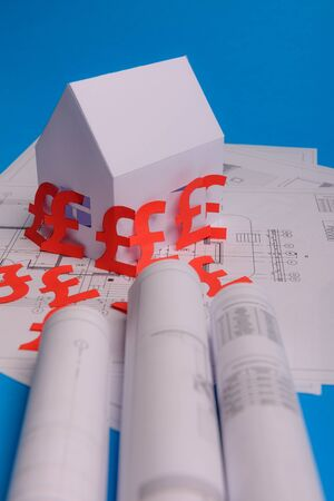 White family paper house , british pound money symbol , house projects plan and blueprints on mint background paper. Minimalistic and simple concept, style. Vertical orientation. View from above. copy space