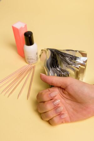 The procedure for removing varnish from nails hybrid nails in progress. Gel nail polish remover foils on womans hands