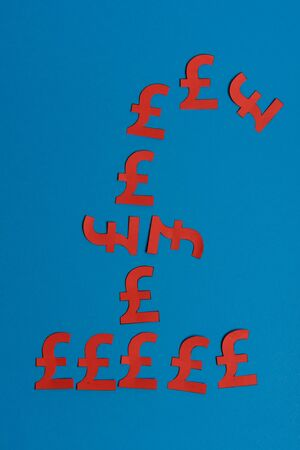 Paper yellow symbols of british pound currency on blue background. View from above with copy space