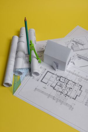 White family paper house, house projects plan and blueprints in the background. Minimalistic and simple concept, style. Horizontal orientation. View from above. Foto de archivo