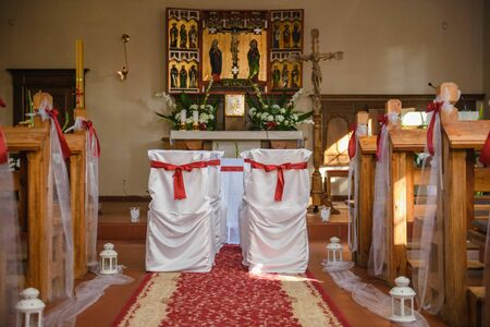 Church sanctuary before a wedding ceremony. Empty chairs for bride and groom