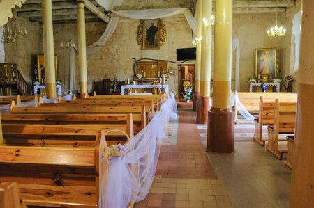 Church sanctuary before a wedding ceremony. Empty chairs for bride and groom Stock Photo - 138925297