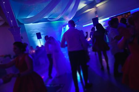 Bride and groom dancing the first dance at their wedding day. Guest on the dancefloor Stock Photo