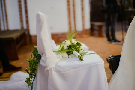 Church sanctuary before a wedding ceremony. Empty chairs for bride and groom Stock Photo - 138927155