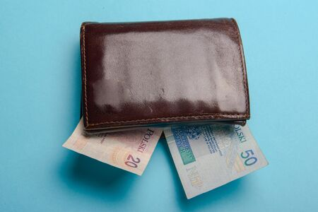 brown mans leather wallet with money bills on a blue background Stock Photo - 138927669