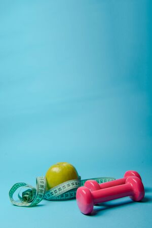 Pair of pink 1 kg dumbbells on blue background and water bottle Stock Photo - 138927160