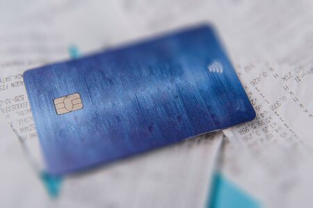 Close-up Of Credit Card On Shopping Receipt On Blue Background
