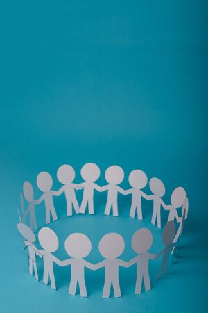 abstract paper people holding for hands on blue background Stock Photo - 138927912