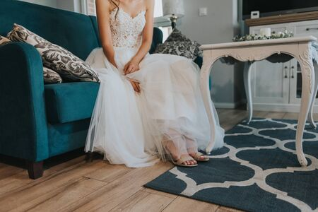 Bridesmaid helping slender bride lacing her wedding white dress, buttoning on delicate lace pattern with fluffy skirt on waist. Morning bridal preparation details newlyweds. Wedding day moments, wear. Stock Photo - 138934361