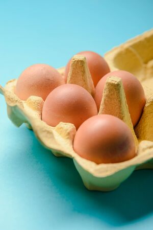 View of opened box of chicken eggs, blue background Stock Photo