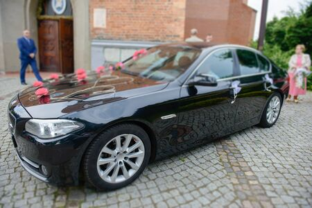 Luxury wedding car decorated with beautiful flowers. Brides and grooms wedding day